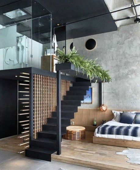 modern loft idea with black staircase ornate wood space divider wood floors concrete walls