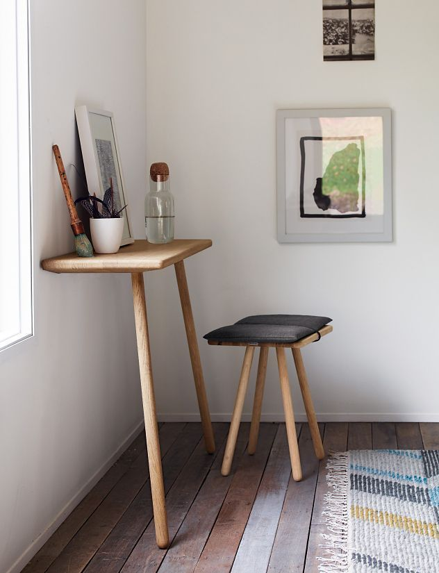 practical small wooden console table with two legs tapered legs wood stool with dark gray cushion