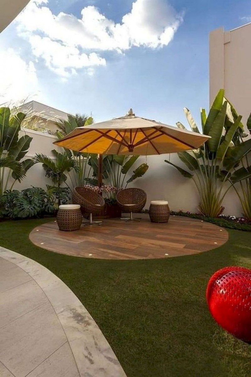 small backyard design in modern style modern outdoor furniture set tropical houseplants outdoor umbrella round wood floors vividly green grass landscape