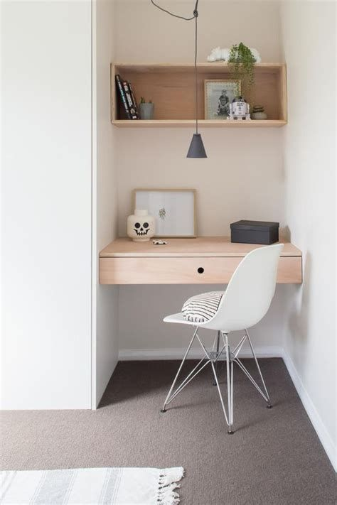 small minimalist home office with light wood working desk tiny white working chair with hairpin legs upper wood shelving unit gray floors