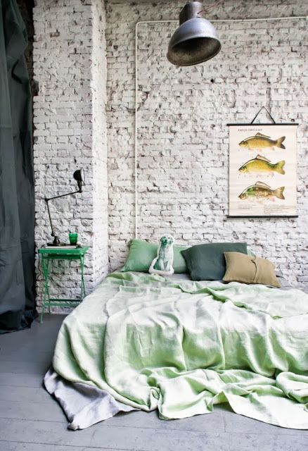 white brick walls ornate fish wall decor green bedside table mint green bed linen