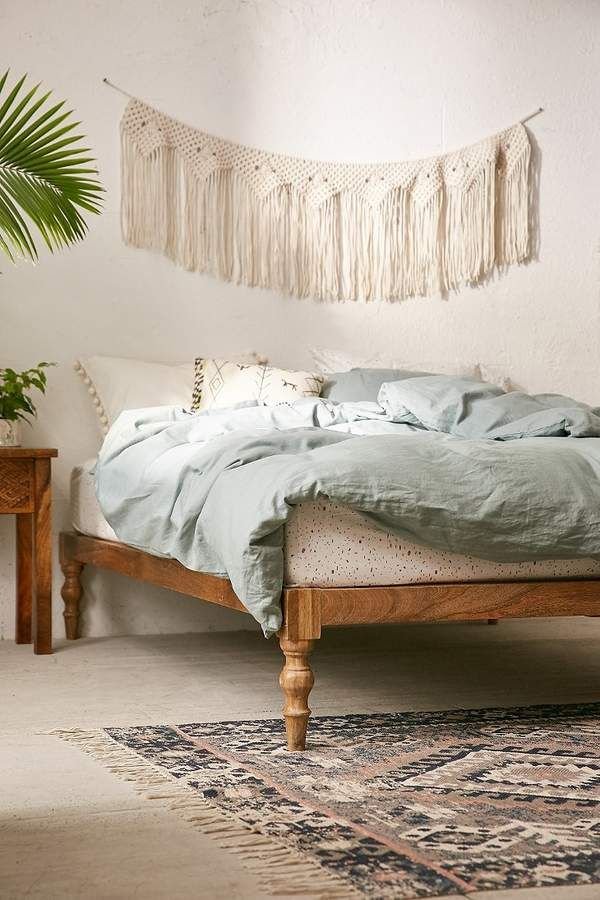 Bohemian style platform bed frame ultra light blue duvet cover macrame wall decor multicolored rug with tassels