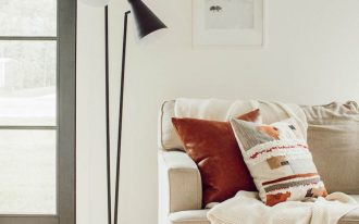 Minimalist living room with dusty white sofa plus Bohemian style throw pillows and white throw blanket two branch floor lamp