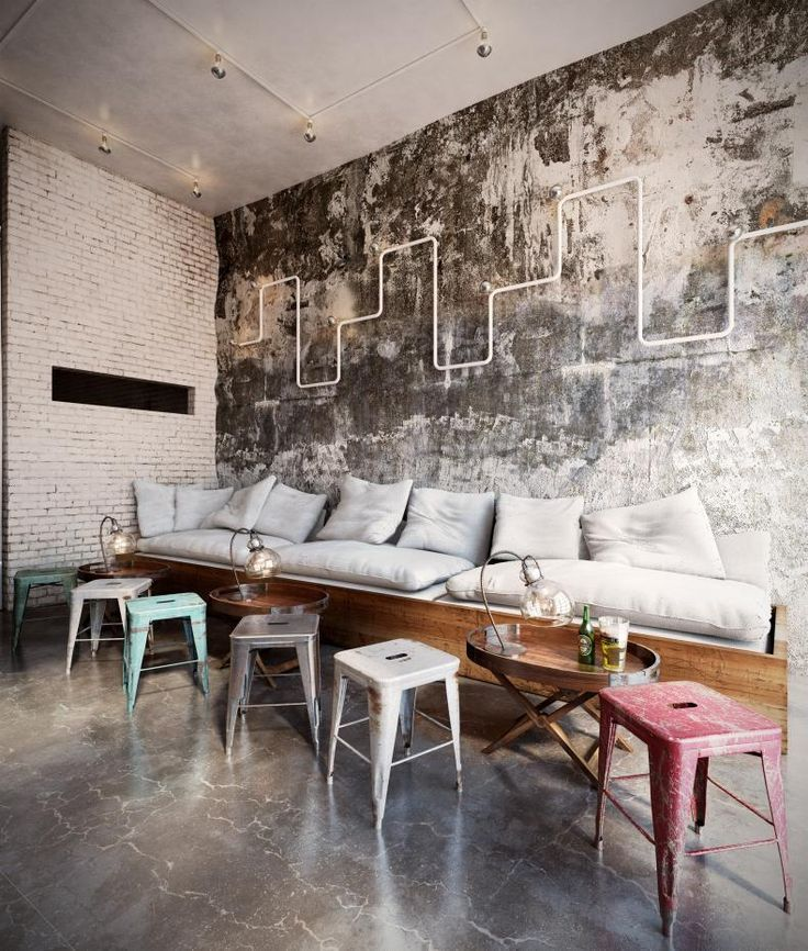 bench seat with cushion and throw pillows shabby plastic stools worn concrete walls white brick walls