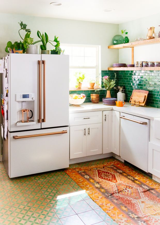 clean and minimalist kitchen design with white cabinets plus brass finish multicolored runner geometric patterned tile floors green subway tile backsplash light wood open shelves