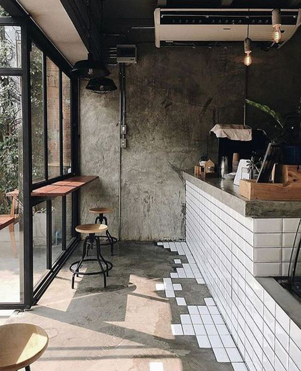 industrial coffee shop interior idea with floating wood bench table with industrial stools concrete floors with white subway tile highlights concrete walls