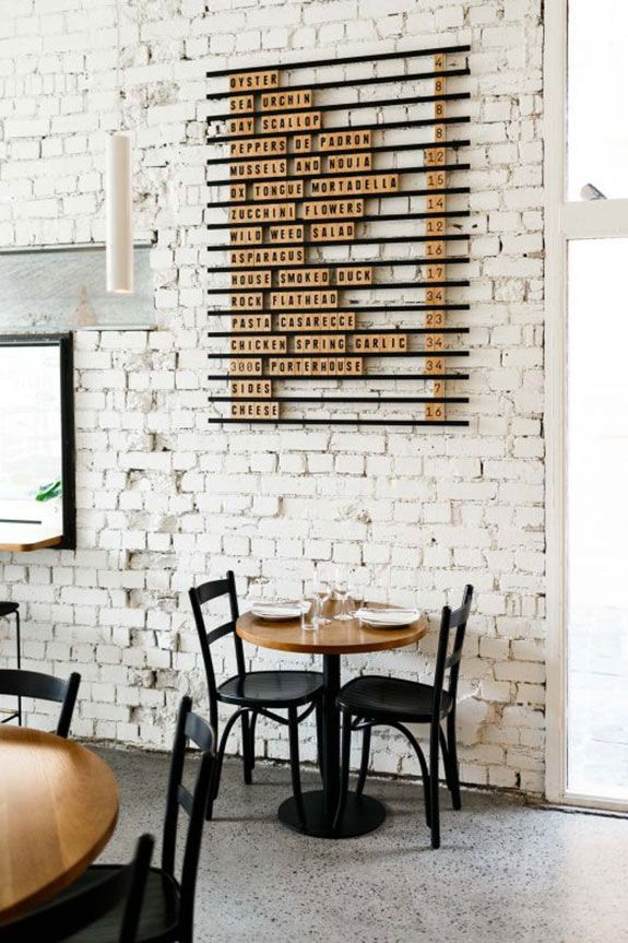 inspiring coffee shop interior with worn white brick walls matte black chairs round wood top table