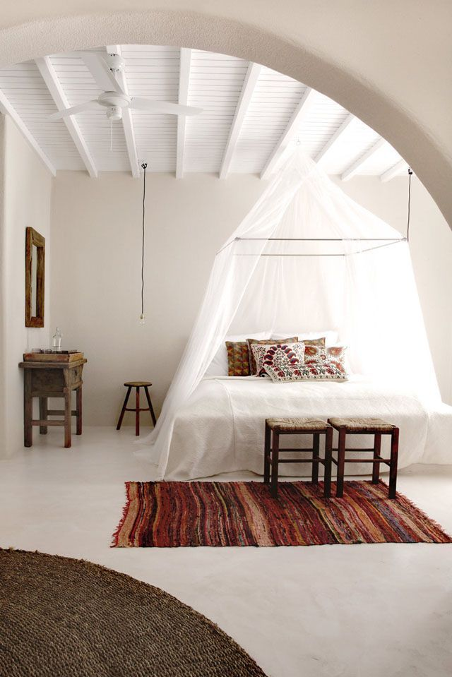 minimalist Bohemian bedroom idea with bed canopy plus pure white bed draperies white bedding set a couple of bed stools bold rug round flat woven rug pure white walls and floors