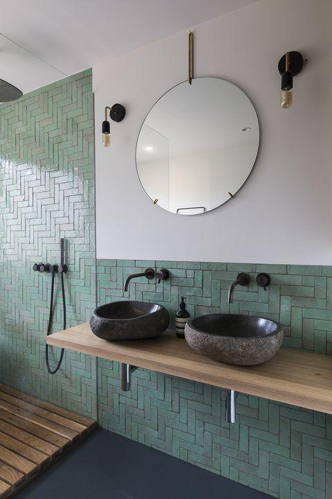 minimalist bathroom design with green pastel subway tile backsplash and wall stone like sinks in natural black natural wood top vanity