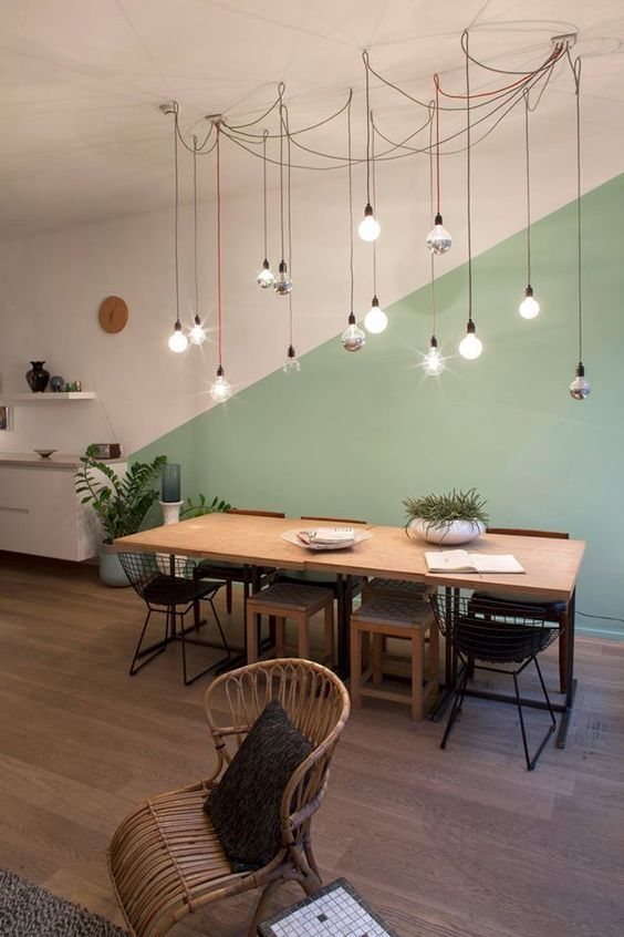 minimalist dining space with pasel green blocking on wall wood dining table mix dining chairs rattan chair