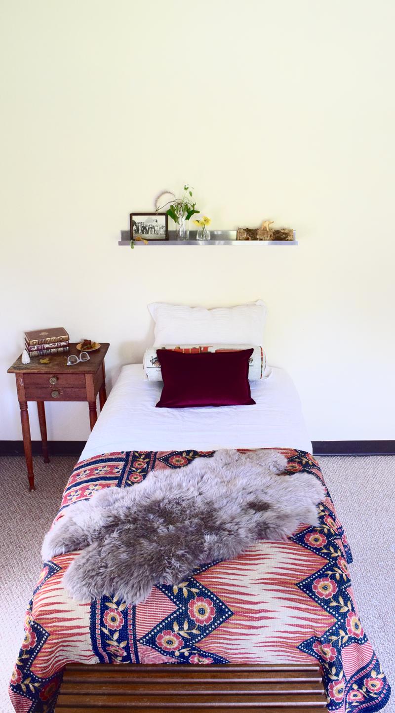 minimalist guest room with Bohemian style blanket gray shag throw blanket dark wood bedside table