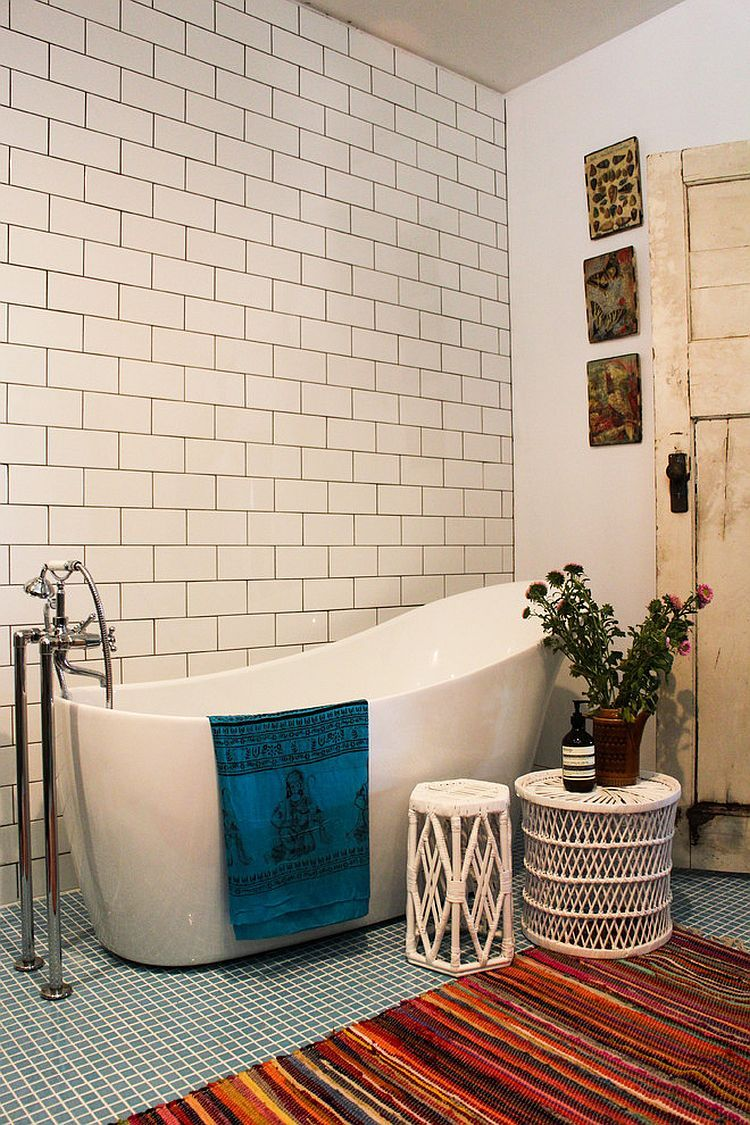 modern minimalist bathroom with white subway tile walls with black grouts modern white bathtub white rattan side tables multicolor rug with bold color stripes
