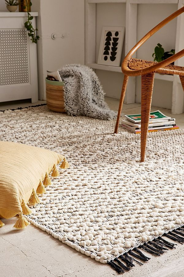 pala textured loop area rug with black tassels yellow floor pillow with tassels