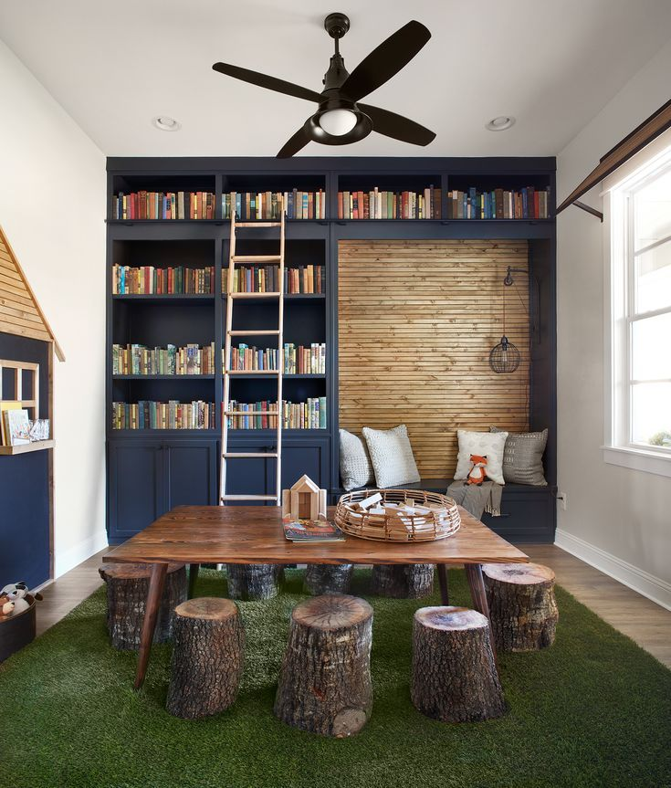 reading nook in modern rustic style huge wooden table tree trunk stools dark blue book rack with ladder bench with throw pillows