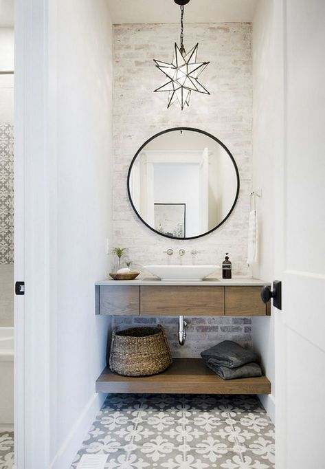 simple industrial bathroom idea with round mirror with black frame wood bathroom vanity with white sink and under shelf whitewashed brick walls geometric tile floors