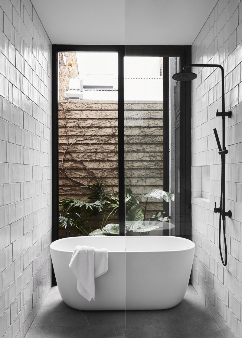 small bathroom in black and white big glass window with black frames white modern bathtub textured white tile walls