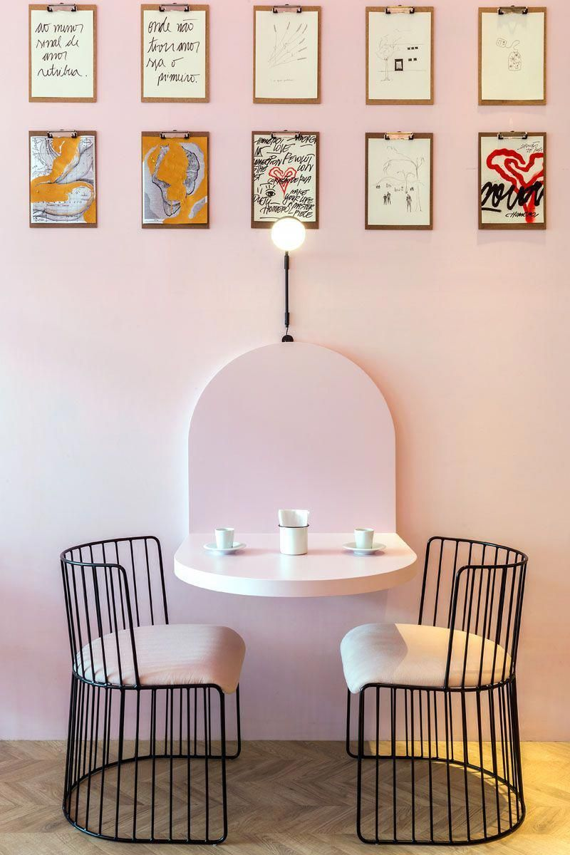 small breakfast nook design with light pink walls wall mounted table in light pink modern black metal chairs with white cushion herringbone wood floors