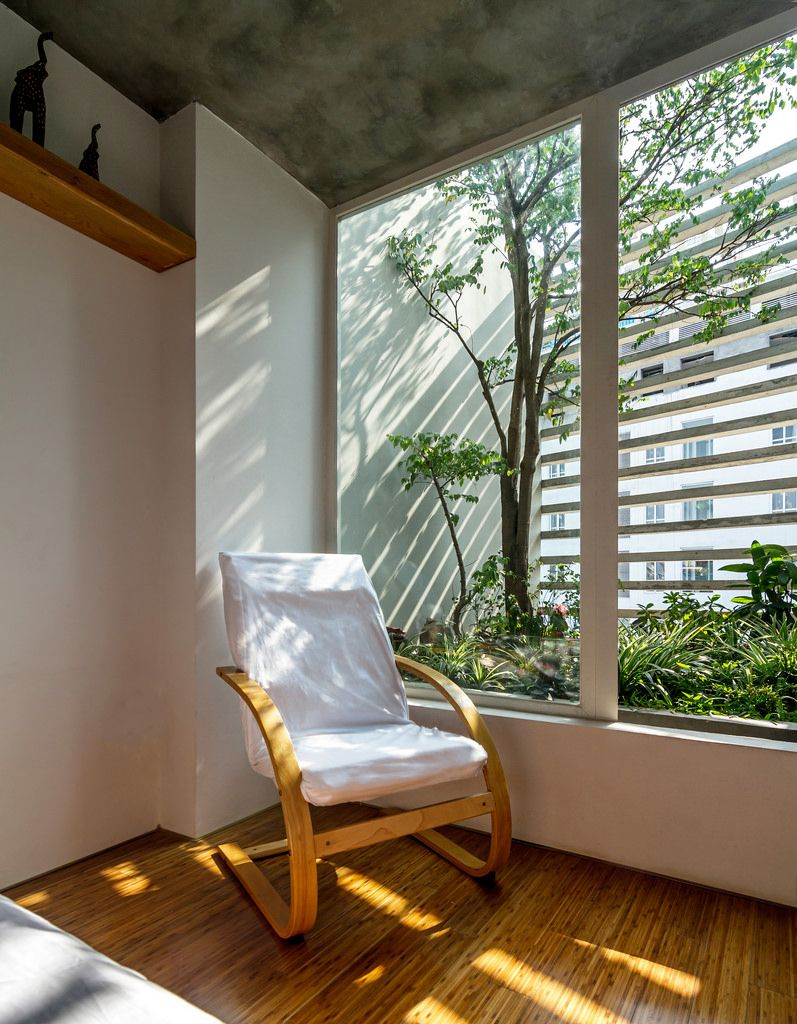 small corner sitting area in minimalist look with minimalist rocking chair with white upholstery interior garden natural wood floors